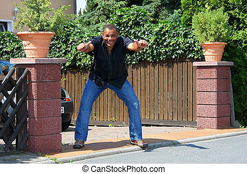 an African American mature man photographed in the summer sun in front of his house posing in a winner´s manner by raising his fists and showing us his attitude, successfulness and contentness