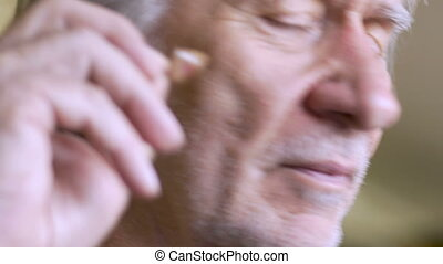An aging senior takes out his hearing aid, checks it and...
