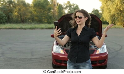 An agitated girl and a broken car on the road. A call to the car service