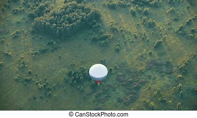 An air balloon flying over the field. Aerial view