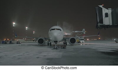An airplane on a courtyard being washed - A white glossy...