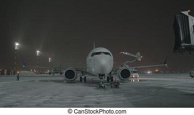 An airplane on an airport courtyard against dark sky - An...