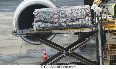 An airport - loading the baggage on the plane using moving belt. Mid shot