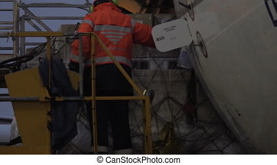 An airport worker on the elevator watching the load delivery