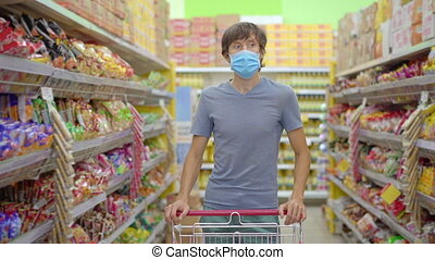 An alarmed man wears a medical mask against coronavirus while purchasing food in a supermarket or store. Quarantine is over, now you can go to the clothing store but have to wear a face mask. Health, safety and pandemic concept.