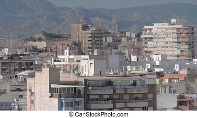 An Alicante urbanscape against mountain slopes on a sunny...