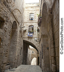 An alley in the Jewish quarter of the old city of Jerusalem, Israel. Hanging from the bottom window is an israel flag with the symbol of Jerusalem instead of the star of David.