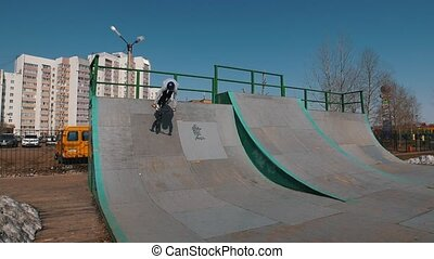 An alone bmx rider in grey hoodie on ramps in the skatepark....