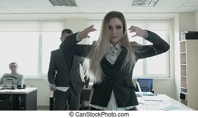 An ambitious businesswoman is dancing freely in the office. A young blonde feminist takes power in the office with the help of a dance.