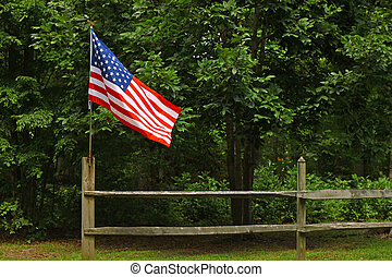 An American flag on a fence post blowing in the wind on a summer day with room for your text