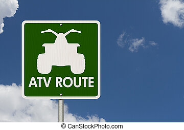 An American road sign with a sky background with a symbol of an ATV and words ATV Route, Places to ride ATV