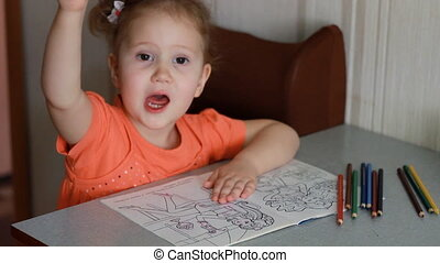 An amusing pretty girl sits at a table and draws in multicolored pencils. Child and creativity.