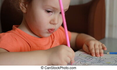 An amusing pretty girl sits at a table and draws in multicolored pencils. Child and creativity. Close-up