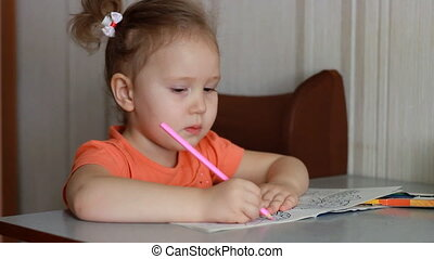 An amusing pretty girl sits at a table and draws in...