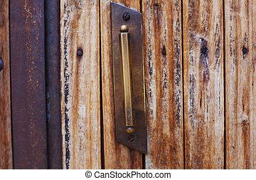 An ancient door handle on wooden door