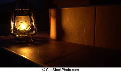 An ancient kerosene lamp stands on the steps of the house lit with a soft yellow light, in the street the night