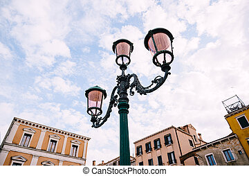 An ancient triple metal street lamp, with pink plafonds against the sky and buildings of Venice, Italy. Vintage street lighting, elegant pillar design.
