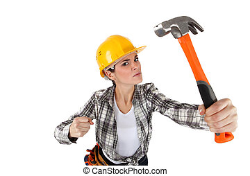 An angry female construction worker with a hammer.