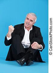 An angry man sitting cross-legged