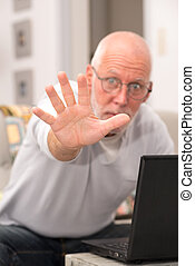 angry senior man using a laptop in home