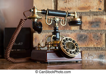 An antique analog telephone set with black box base and golden ringer, and handset