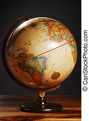 An antique globe on a table with a dark grey background