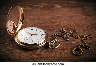 An antique gold pocket watch lies on a wooden table