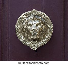 An antique lion head pull handle knob on a vintage wooden red door. Architecture in Valletta, Malta.