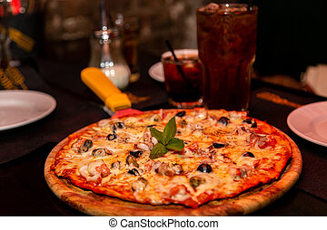 An appetizing pizza with seafood and cheese lies on a wooden plate on the table. With a cold brown iced drink.