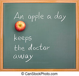 An apple a day keeps the doctor away, words on blackboard.