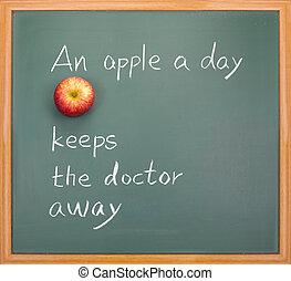 An apple a day keeps the doctor away, words on blackboard.