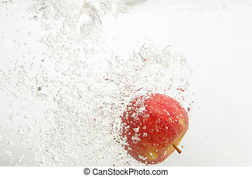 An apple is dropped into water.