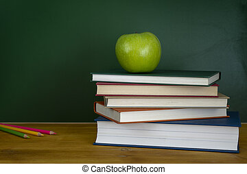 An apple on top of a pile of books. Blank chalkboard on the background.