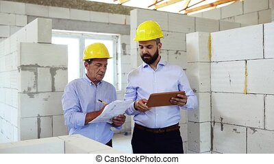 An architect and home owner at the construction site. -...