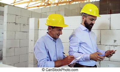 An architect and home owner at the construction site. - ...