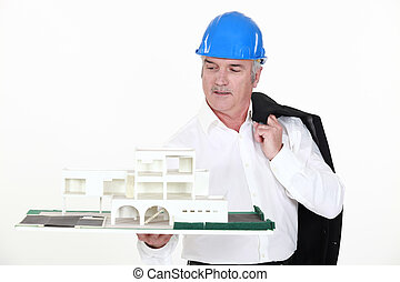 An architect holding a miniature.