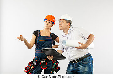 An architect man wearing a hard hat or helmet and co-worker builder woman reviewing blueprints