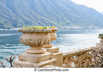 An architectural flowerpot on a stone fence against the backdrop of water and mountains.