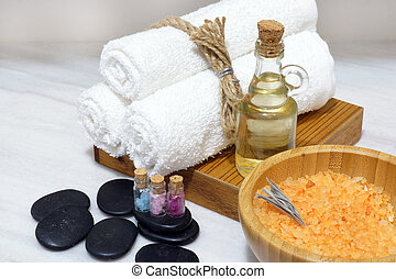 An aromatic oil, soft towels, hot stones and bath salt in a wooden bowl with a spoon make up a set for Spa procedures
