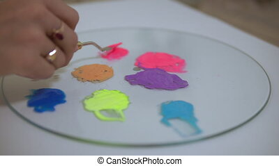 An artist combines colours on the palette - Preparation of...