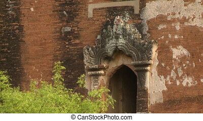 A close up shot of the artistically designed arch of the entrance of an ancient building with red bricks