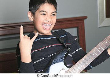 Asian boy play guitar in his bedroom
