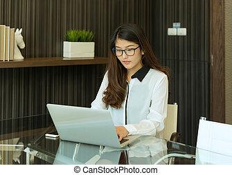 An Asian business woman using a laptop