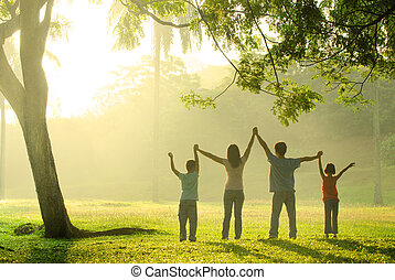an asian family jumping in joy in the park during a...