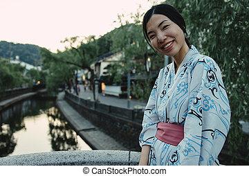 an asian girl smiling and wearing Yukata