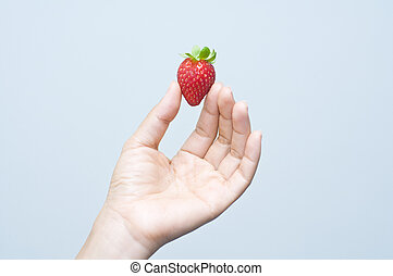 an asian hand holding a single strawberry