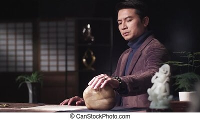 An Asian man meditating in room