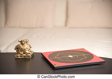 An asian symbol and a Feng Shui compass on a table