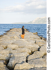 asian woman standing on rocks
