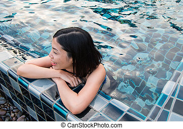 an asian young woman in the swimming pool